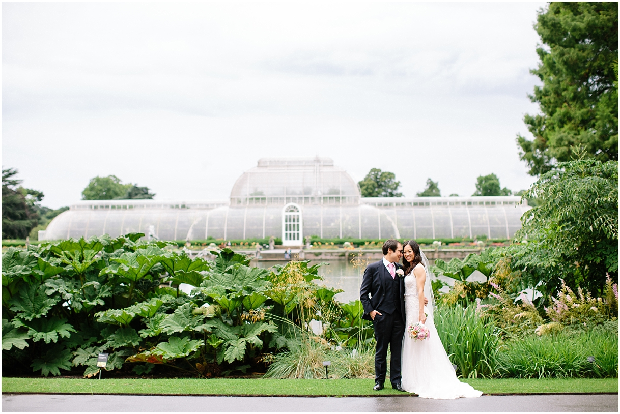 Bride and groom outside greenhouse at Kew Gardens