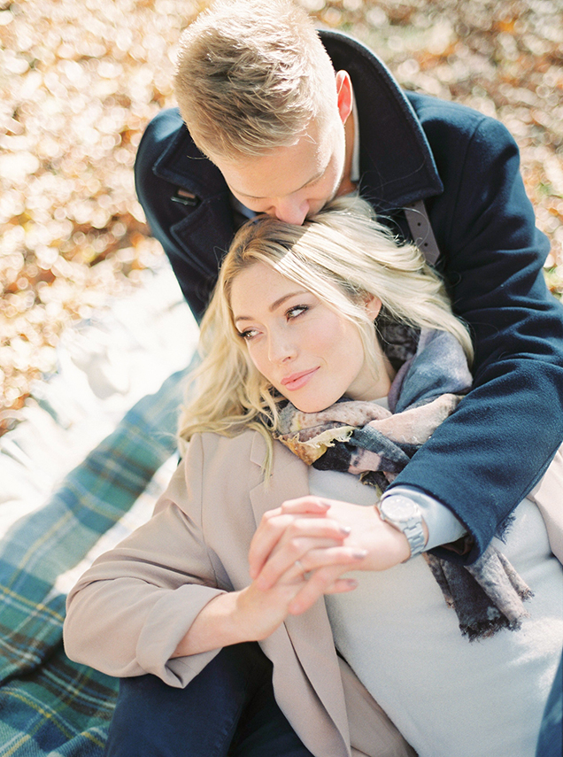 Romantic and beautiful engagement shoot captured on film. Couple lying on blanket.