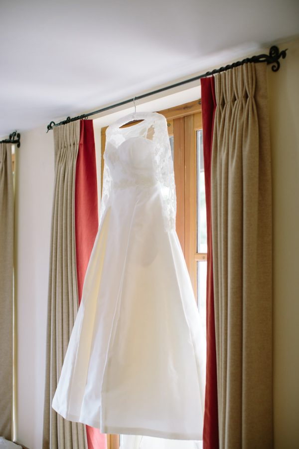 Sassi Holford wedding dress hanging in window