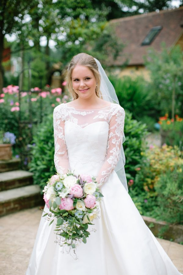 Natural and elegant photograph of bride holding wedding bouquet by Stansted House wedding photographer