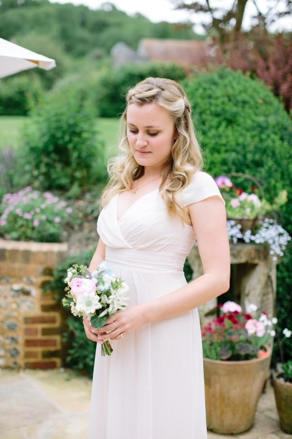 Bridesmaid wearing pale pink dress holding natural wedding bouquet