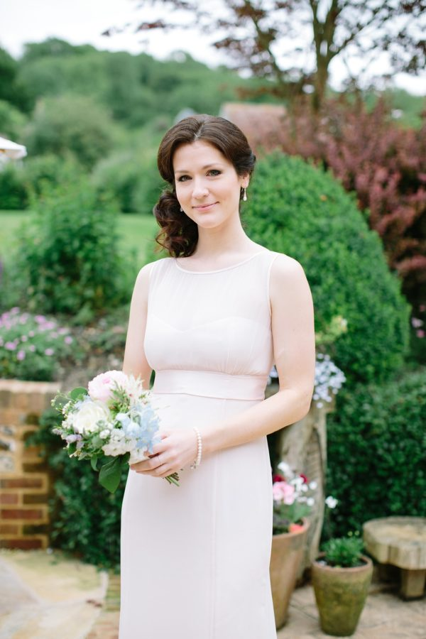 Bridesmaid wearing pale pink dress holding bouquet