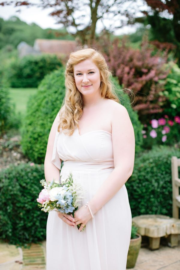 natural portrait of bridesmaid in pale pink dress by Stansted House wedding photographer
