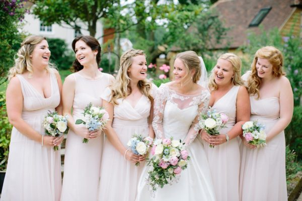 Bride laughing with bridesmaids captured in a natural fine art style by Stansted House wedding photographer Camilla Arnhold