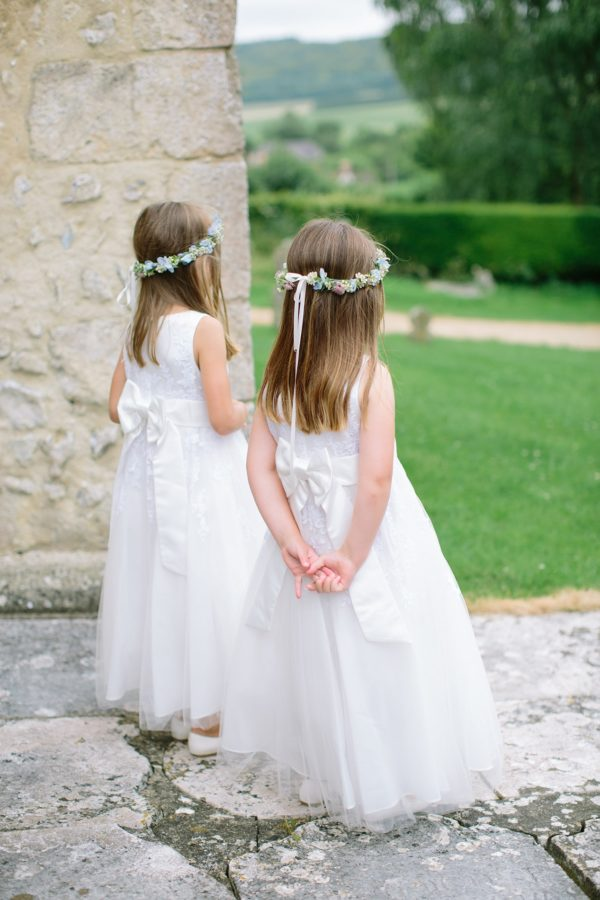 Flower girls wearing flower crowns waiting for the arrival of the bride