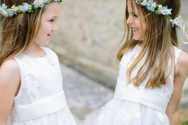 Flower girls smiling at each other wearing white dresses and flower crowns