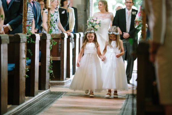 flower girls walking down the aisle captured by Stansted House wedding photographer