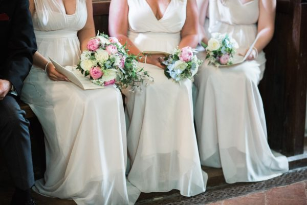 Detail photograph of bridesmaids pink dresses and bouquets in church wedding service