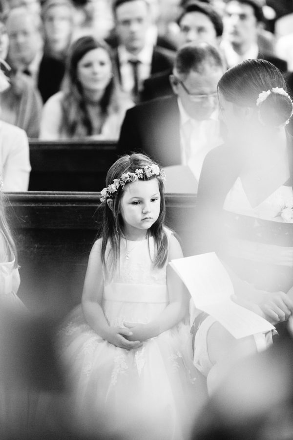 Black and white photograph of flower girl during wedding ceremony