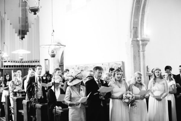 Wedding guests singing hymns during wedding ceremony