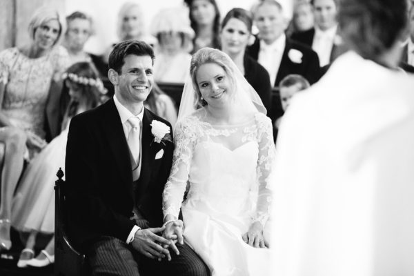 Black and white photograph of bride and groom smiling at vicar during wedding service by Stansted House wedding photographer