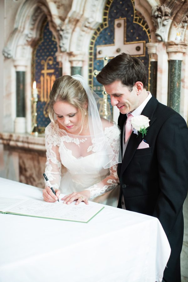 Bride and groom signing the register at the end of wedding ceremony