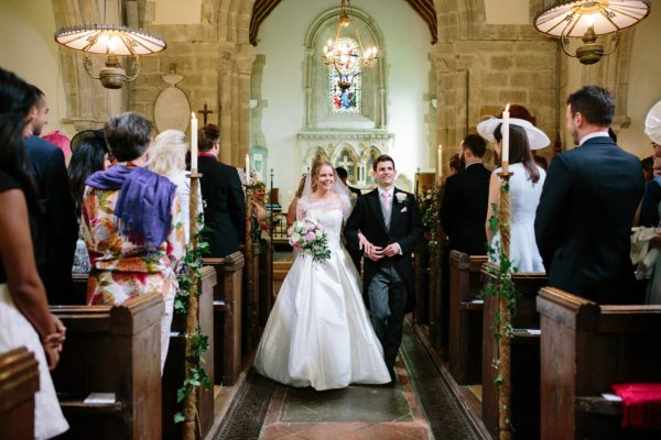 Bride and groom smiling leaving church