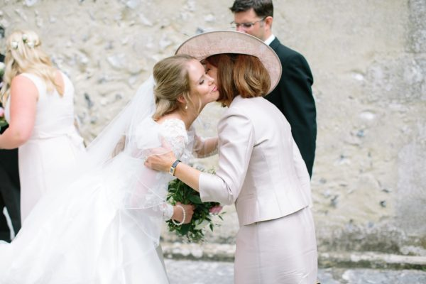 Bride kissing her mother after wedding ceremony