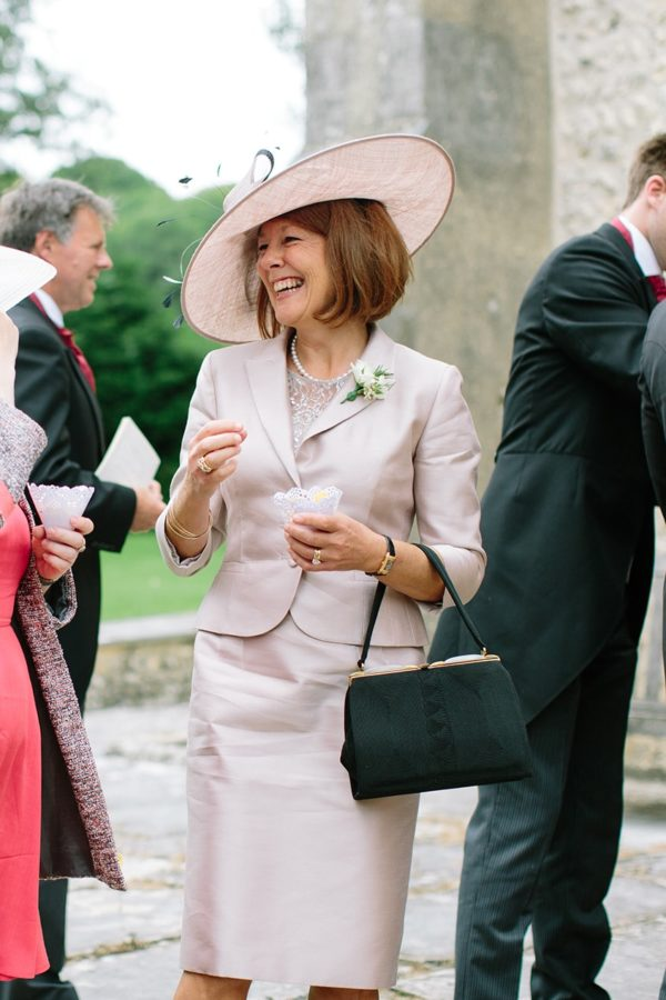 Mother of the bride wearing blush suit laughing at church