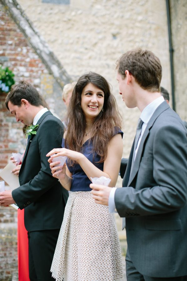 Wedding guest smiling and holding confetti outside church