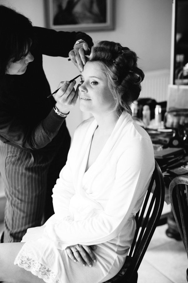 Black and white photograph of bride having her make up done on a wedding morning