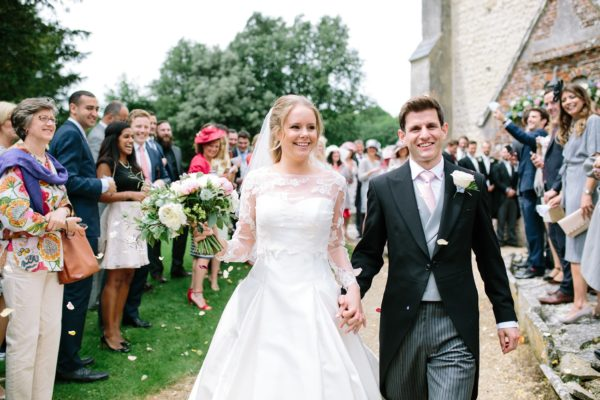Bride and groom smiling and walking through confetti captured by Stansted House wedding photographer Camilla Arnhold