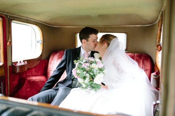 Bride and groom in the back of wedding car kissing