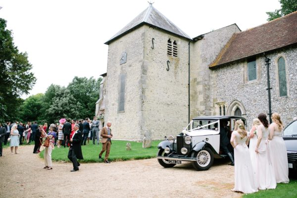 Guests waving to bride and groom leaving in wedding car