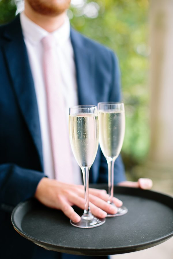Two glasses of champagne on a tray at the entrance to Stansted House captured by Stansted House wedding photographer