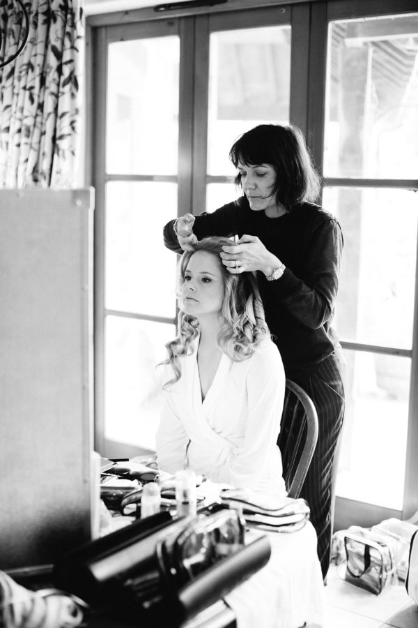 Black and white photograph of bride having her hair done on morning of wedding captured by Stansted House wedding photographer