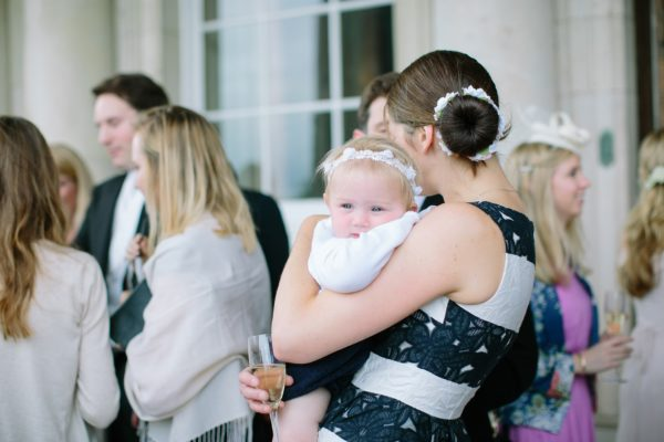 Wedding guest holding baby at Stansted House wedding