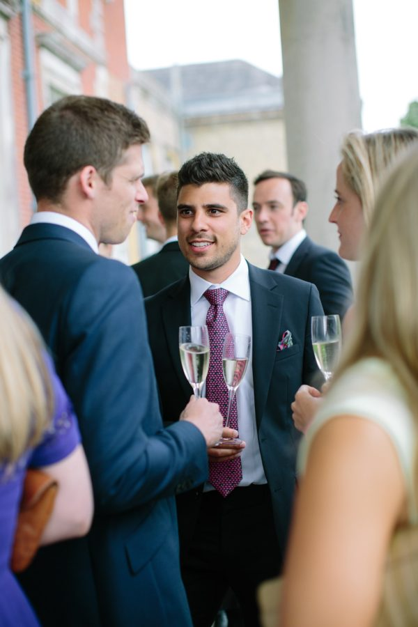 wedding guest chatting and drinking champagne at Stansted House wedding