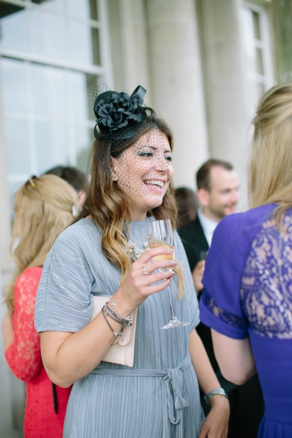Wedding guest smiling and talking photographed by Stansted House wedding photographer