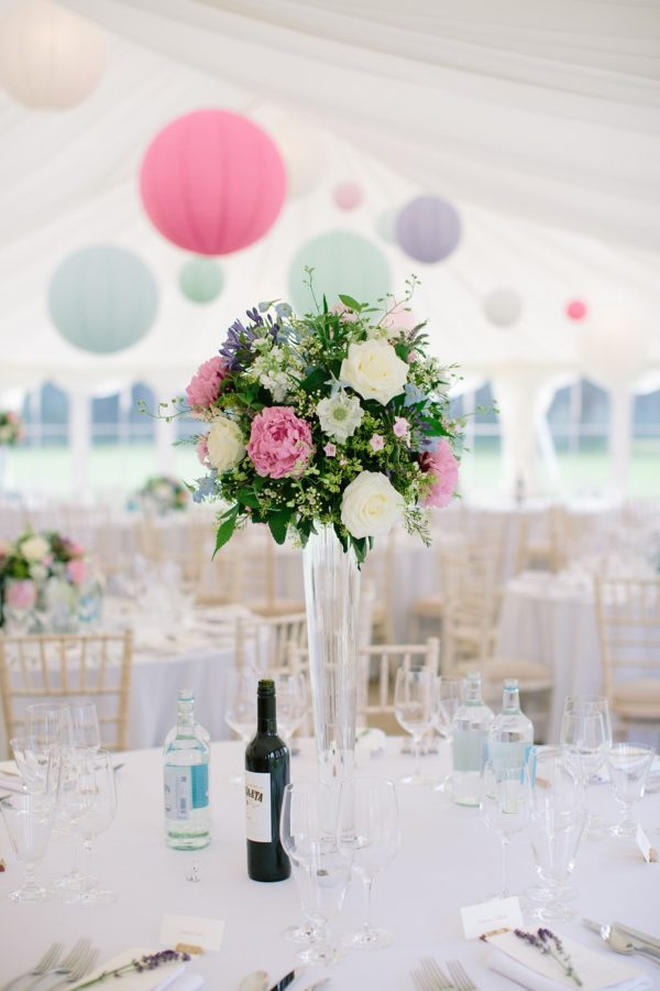 Pastel coloured wedding flowers and hanging lanterns in marquee at Stansted House wedding