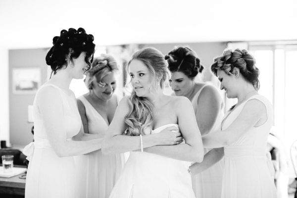 Black and white photograph of bride putting on Sassi Holford wedding dress on the morning of her Stansted House wedding