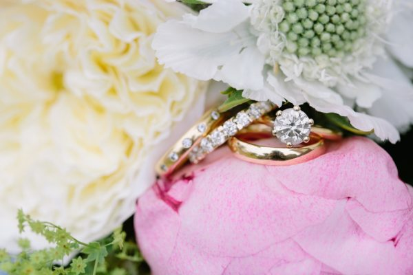 Diamond engagement and wedding rings amongst wedding flowers captured by Stansted House wedding photographer