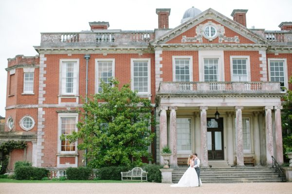 Bride and groom kissing outside Stansted House