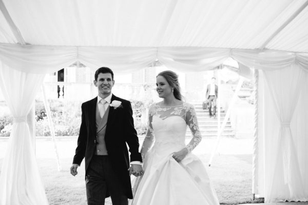 Bride and groom walking into their marquee at Stansted House wedding