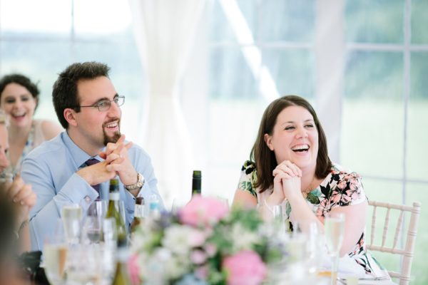Guests laughing during wedding speeches captured by Stansted House wedding photographer