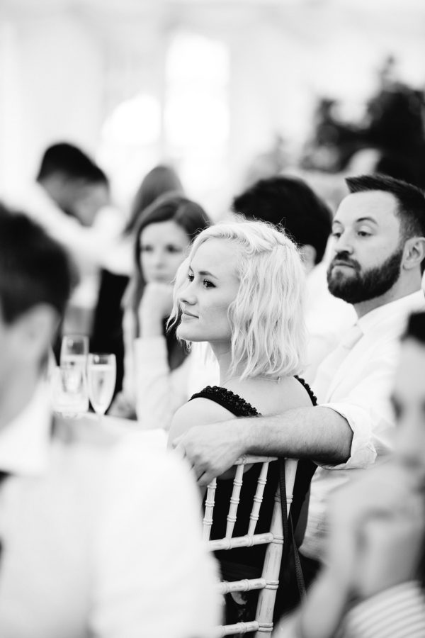 Black and white photograph of guest during wedding speeches at Stansted House wedding