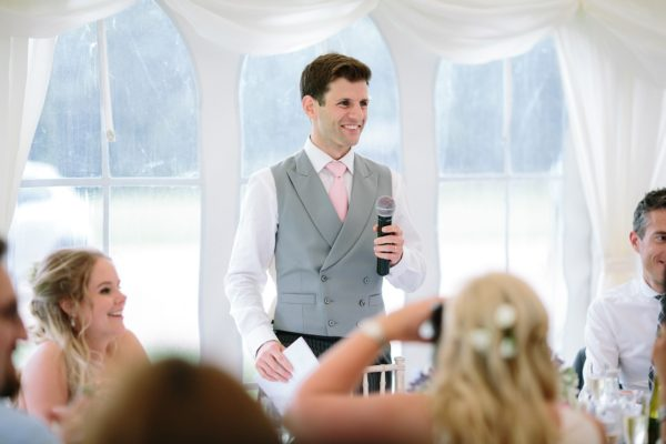Groom smiling and giving wedding speech at Stansted House, West Sussex