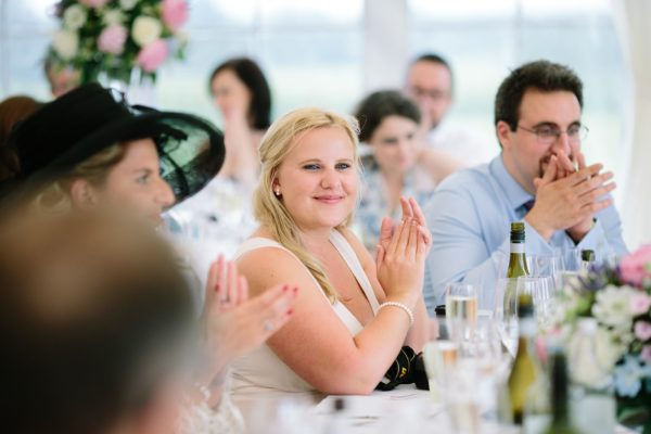 Wedding guest clapping during speeches at Stansted House wedding