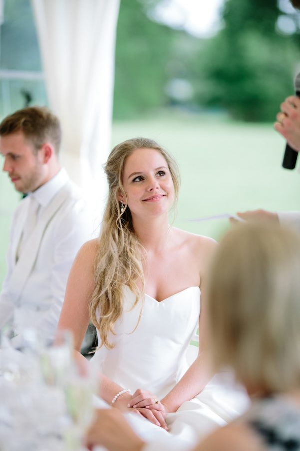 Emotional photograph of bride looking at groom during his wedding speech captured by Stansted House wedding photographer