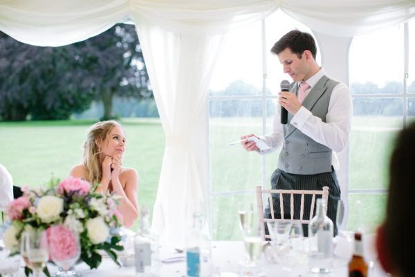 Bride smiling lovingly at groom during wedding speeches at Stansted House wedding