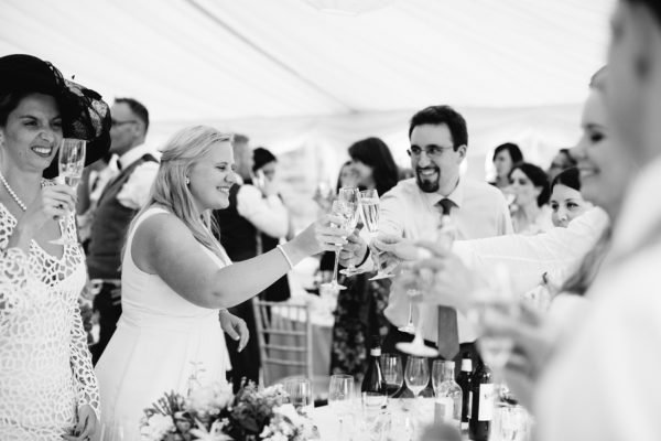 Black and white photograph of guests toasting during speeches at Stansted House wedding