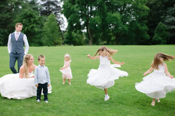 Flower girls spinning around on the lawn of Stansted House