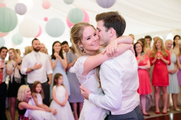 Bride being kissed on the cheek by groom captured by Stansted House wedding photographer