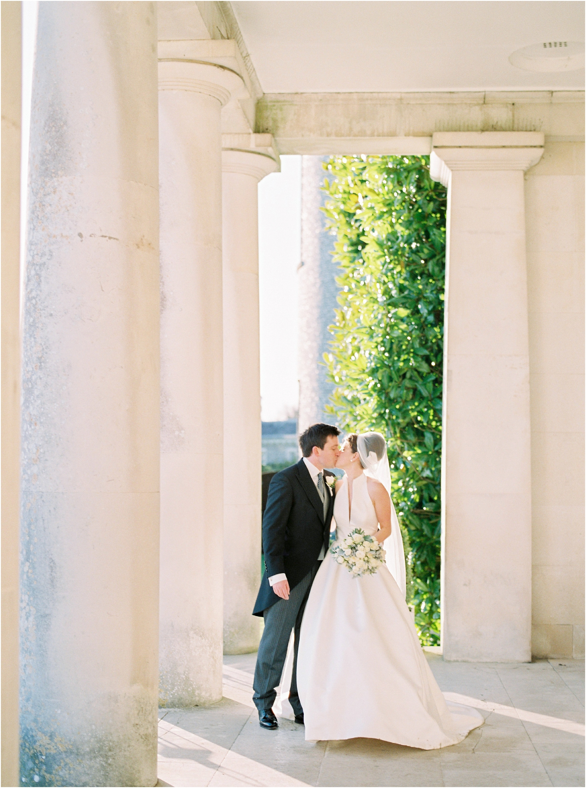 Bride and groom kissing outside Goodwood House
