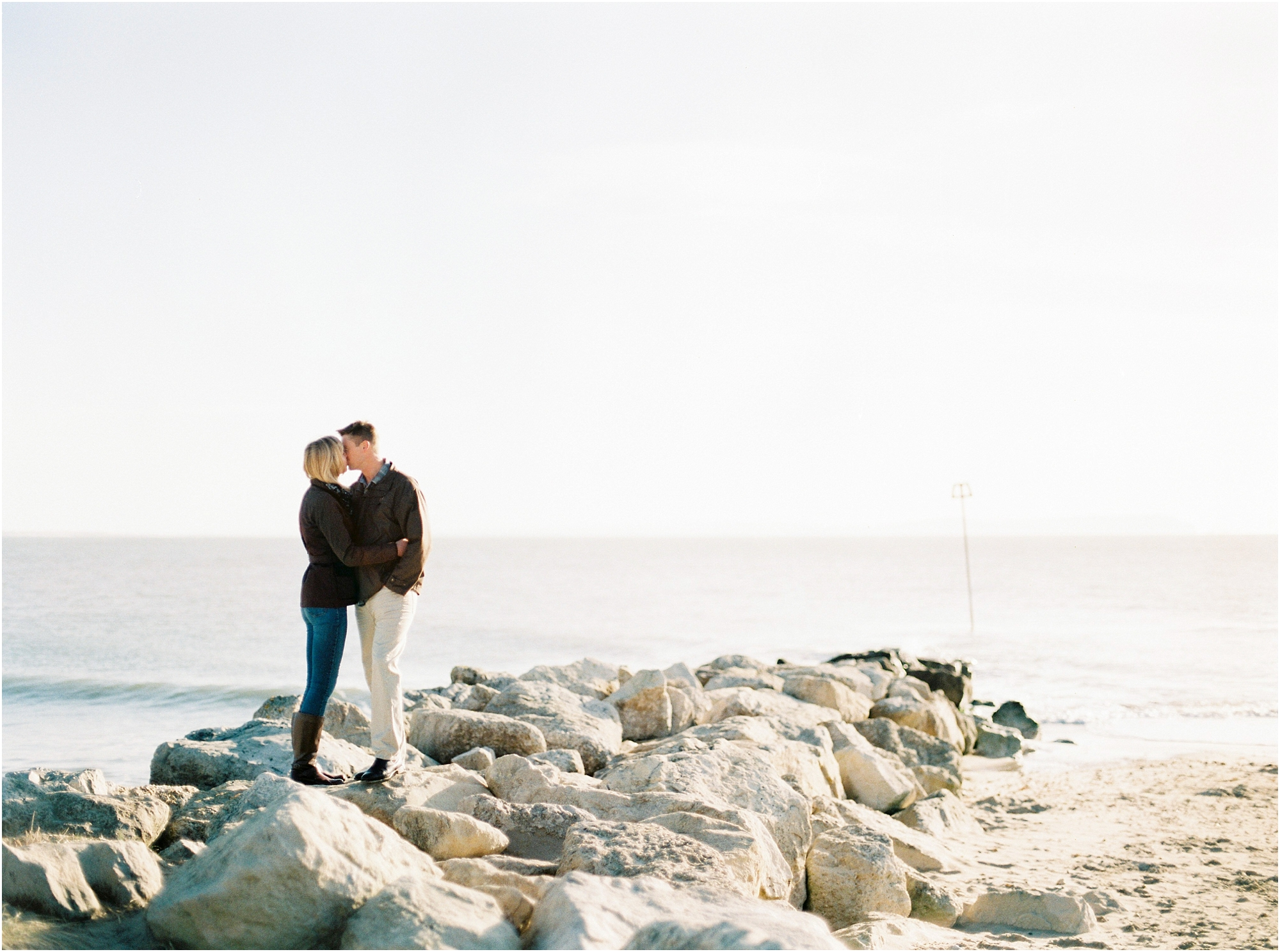 Couple kissing on rocks at Hengistbury Head