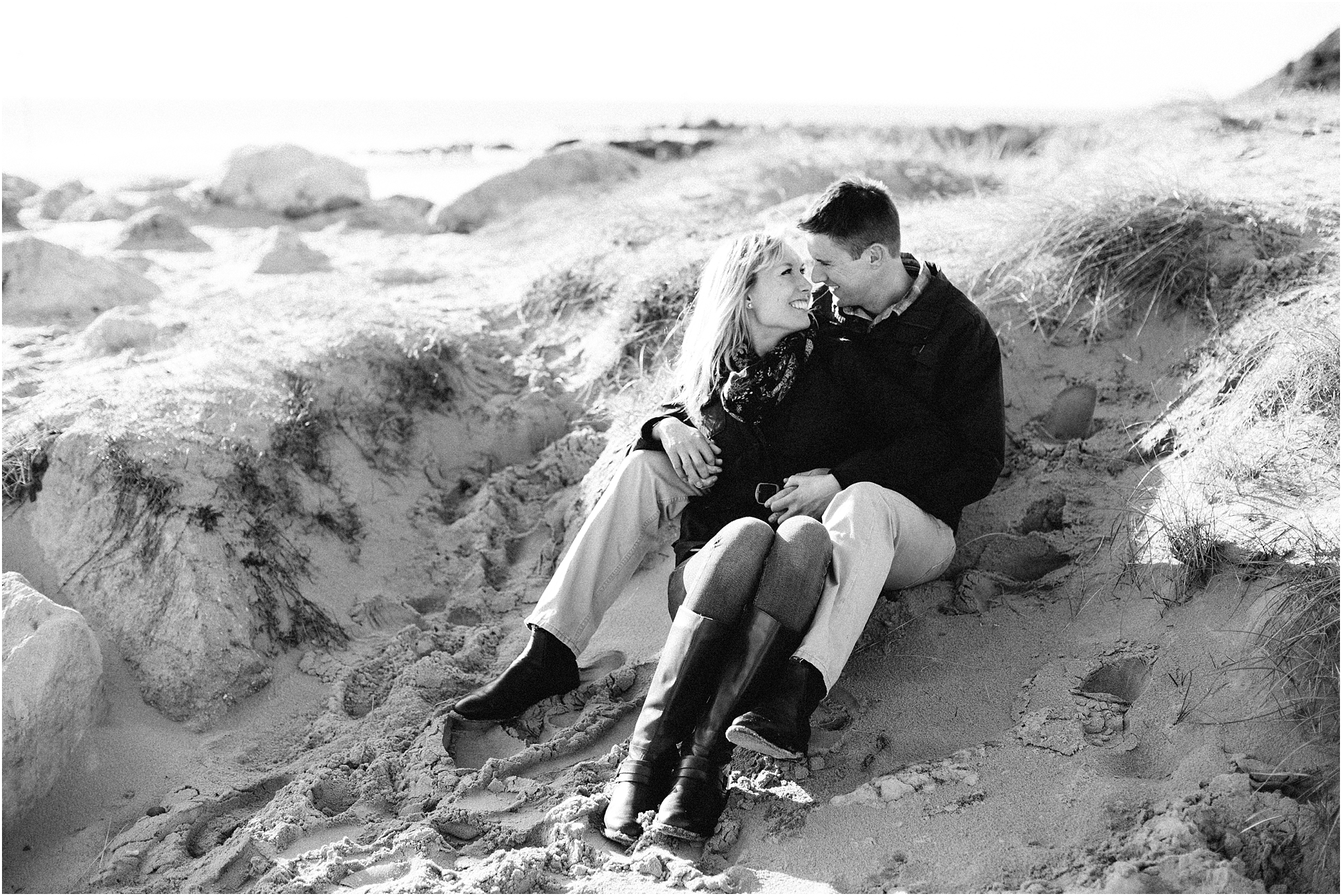 Black and white photo of couple sitting in sand dunes
