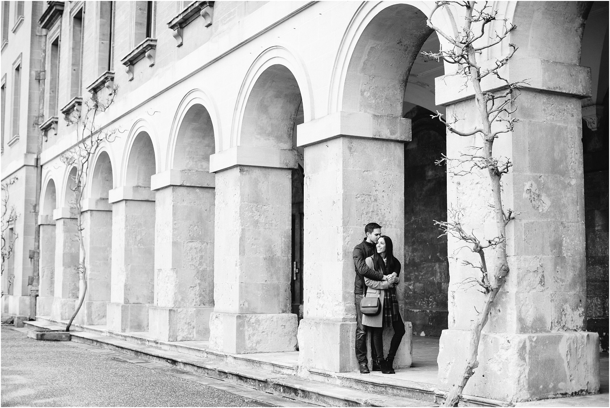 black and white photo of couple cuddling in a archway
