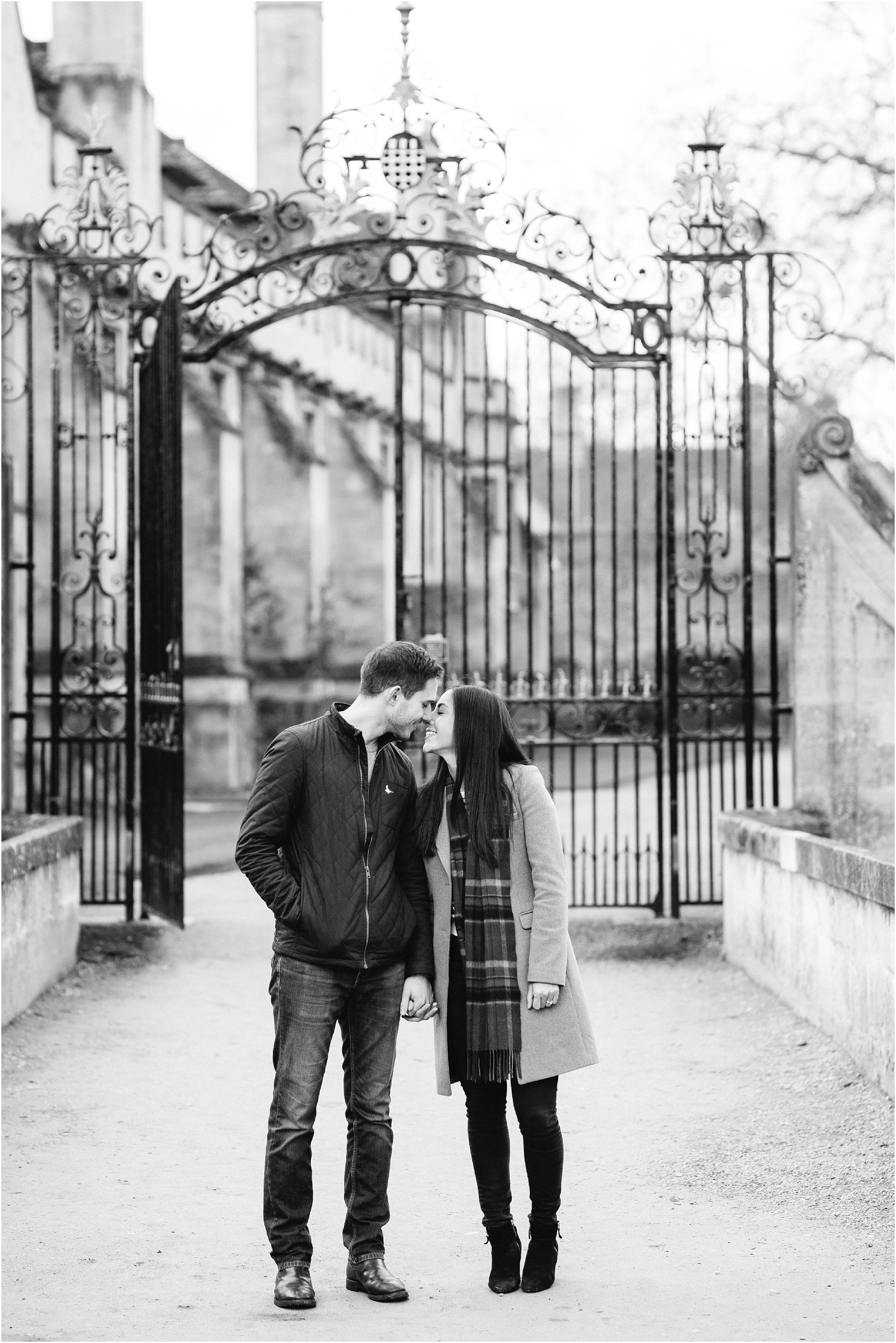 black and white photo of couple kissing in front of gate at Magdalen College Oxford