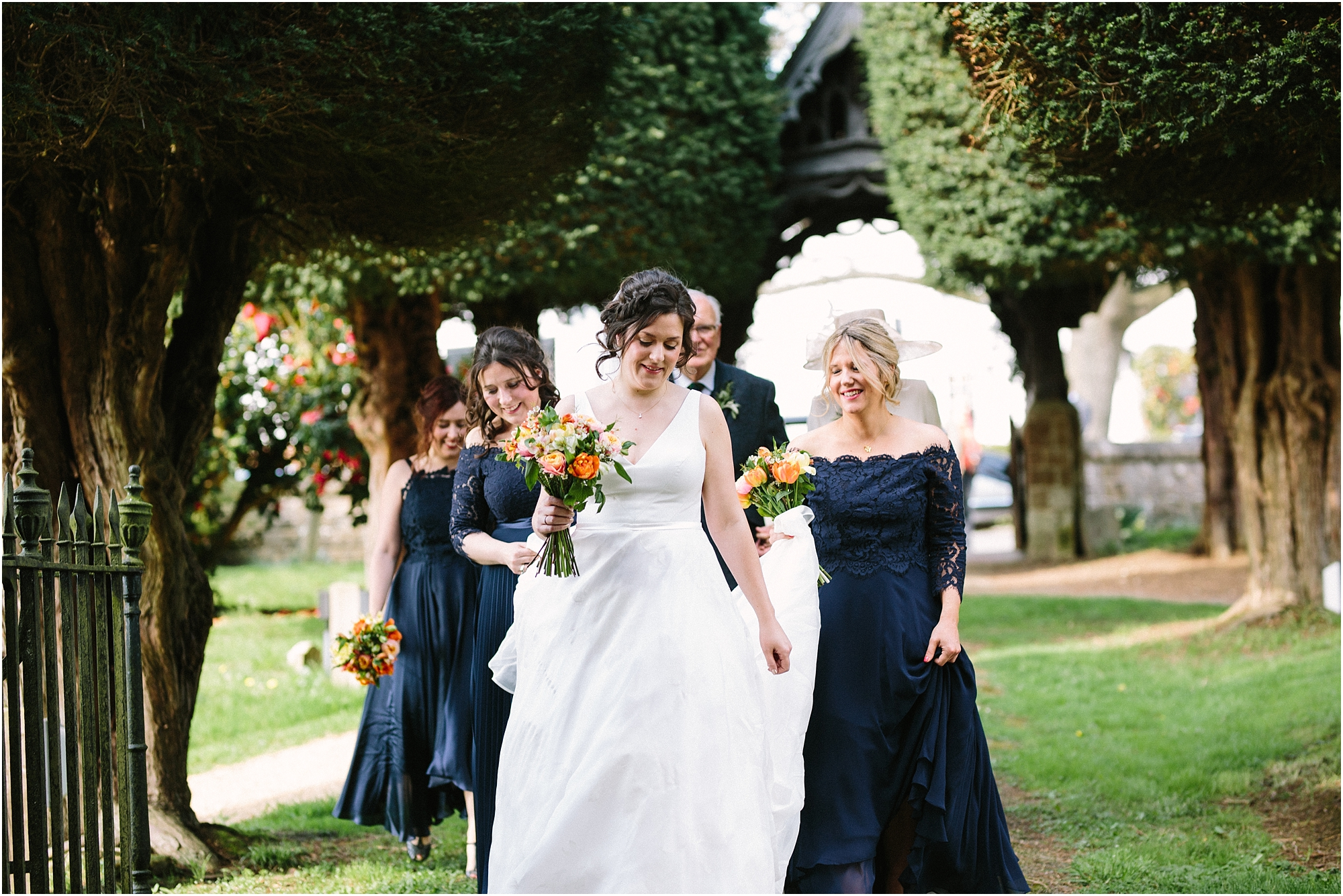 bride walking to church with bridesmaids