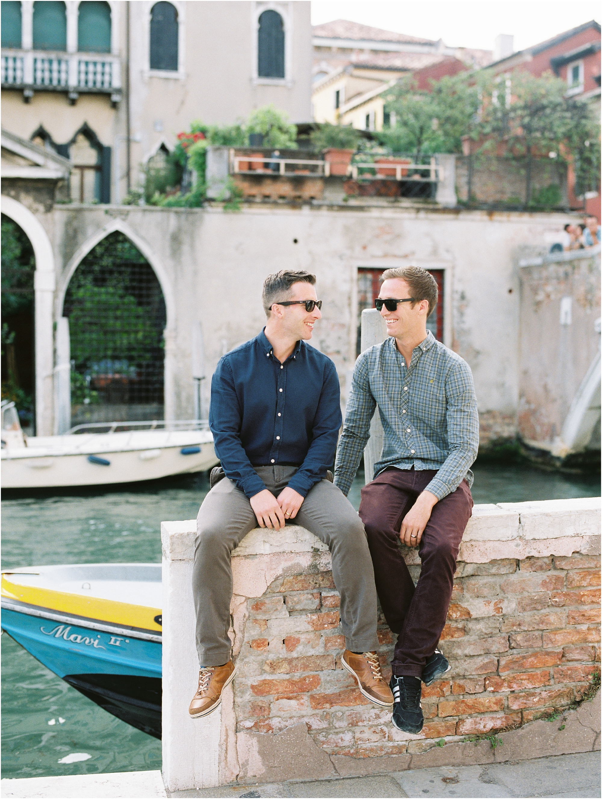 Same sex couple sitting on wall in Venice Italy